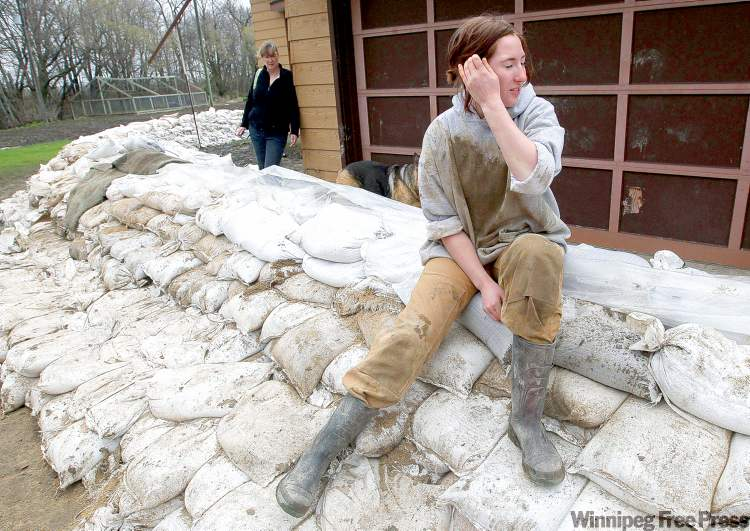 Sam Connery takes a break Wednesday after working to protect her family's home near Hoop and Holler Bend.
