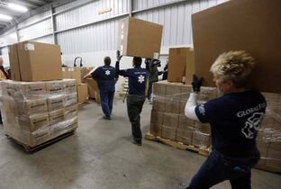 Volunteers from the Manitoba chapters of GlobalMedic and GlobalFire help load supplies destined to help fight the Ebola outbreak in West Africa.