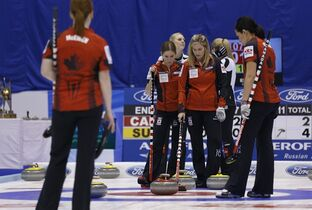 Canada's Jennifer Jones, second right, talks with Kaitlyn Lawes, second left, during the 8th end of the final match of the women's World Curling Championships in Sapporo, northern Japan, Sunday, March 22, 2015. Canada was defeated by Switzerland 3-5. (AP Photo/Shizuo Kambayashi)