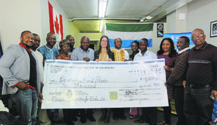 March 20, 2015 - Janelle Delorme (centre), animator of Development and Peace for the region of Manitoba, receiving a cheque from Allieu Sesay (left), President of SALNAM, and  Dr. Ismail Yumkella, Chairman of the SALNAM Ebola Campaign Committee (right), among members of the SALNAM Ebola Campaign Committee.