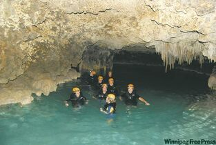 A tour group explores Rio Secreto�s fascinating naturally formed passages and crystal waters.