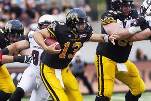 Hamilton Tiger-Cats quarterback Dan LeFevour, centre, runs the ball against the Ottawa RedBlacks during their CFL home opener in Hamilton, Ont., Saturday, July 26, 2014. THE CANADIAN PRESS/Aaron Lynett