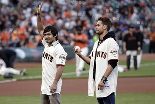 Boxers Manny Pacquiao, left, and Chris Algieri prepare to throw ceremonial first pitches during before a baseball game between the San Francisco Giants and the Milwaukee Brewers on Friday, Aug. 29, 2014, in San Francisco. (AP Photo/Marcio Jose Sanchez)