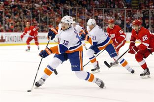 New York Islanders left wing Josh Bailey (12) shoots against the Detroit Red Wings during the first period of an NHL hockey game in Detroit Friday, Dec. 19, 2014. (AP Photo/Paul Sancya)