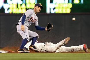 Detroit Tigers second baseman Ian Kinsler, top, awaits the throw as Minnesota Twins' Aaron Hicks steals second base in the fourth inning of a baseball game, Wednesday, Sept. 17, 2014, in Minneapolis. (AP Photo/Jim Mone)