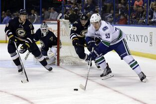 Vancouver Canucks' Bo Horvat, right, controls the puck as St. Louis Blues, from left, Jay Bouwmeester, Brian Elliott and Dmitrij Jaskin, of Russia, defend during the first period of an NHL hockey game Monday, March 30, 2015, in St. Louis. (AP Photo/Jeff Roberson)