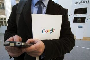 FILE - In this Dec. 10, 2013 file photo, a reporter uses his smartphone during a presentation for the new Google cultural institute in Paris. More Google search requests are now being made on mobile devices than personal computers in the U.S. and many other parts of the world. The milestone was announced at a digital advertising conference on Tuesday, May 5, 2015. (AP Photo/Jacques Brinon, File)