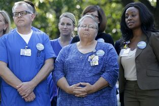 Amy Mullins, center, Kendra Stewart, right, and Randy Joslin join other Texas Health Presbyterian Hospital workers looking on during the reading of a statement outside their hospital, Monday, Oct. 20, 2014, in Dallas. Ebola patient Thomas Eric Duncan was treated at Texas Health Presbyterian Hospital. (AP Photo/LM Otero)
