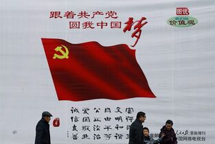 In this Friday, Feb. 27, 2015 photo, a Chinese family walk past a China Dream billboard, showing messages pushed by Chinese President Xi Jinping's administration on display in Beijing. China on Saturday, Feb. 28 cut interest rates for the second time in three months, adding to signs that Chinese leaders are worried that the economic slowdown is deepening too sharply. (AP Photo/Andy Wong)
