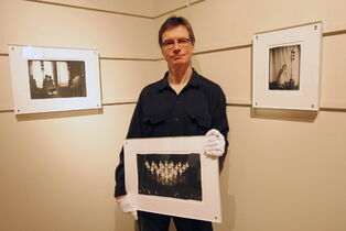 Bruce Monk holds a photo from a show at Mayberry Fine Art in 2010.