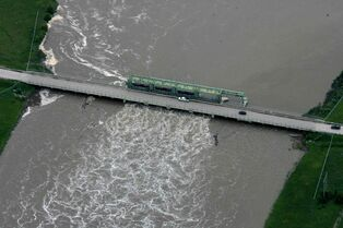Heavy rains in western Manitoba and Saskatchewan recently have raised the level of the Assiniboine River, causing it to overflow its banks, flooding roads and farmers' fields. Aerial photo of bridge over the  Portage diversion dam just west of town where water is diverted north to Lake Manitoba.