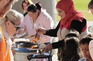 Baraa Diab and her family are served by volunteers during a KidBridge Thanksgiving feast. KidBridge launched their