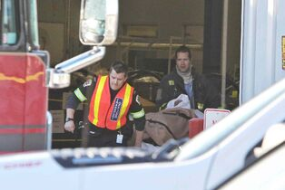 An employee at Standard Aero is brought out to an ambulance after an explosion occurred at the industrial facility this morning.