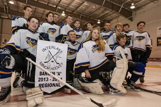 Members of the Stonewall Blues hockey team receive their championship banner in Stonewall on Thursday.