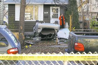 Ruth Bonneville / Winnipeg Free Press A homeowner surveys the damage after a crash on Banning Street early Saturday. Charges are pending against a man involved in the incident.