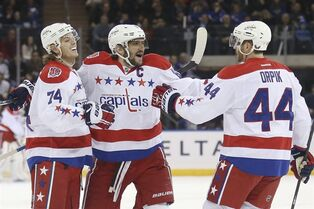 Washington Capitals left wing Alex Ovechkin, center, celebrates after scoring with defensemen John Carlson (74) and Brooks Orpik (44) during the first period of an NHL hockey game against the New York Rangers, Sunday, March 29, 2015, in New York. (AP Photo/John Minchillo)