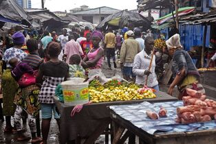 People buy foods at a local market after Liberian authorities reopened the West Point slum where tens of thousands of people were barricaded amid the country's Ebola outbreak in Monrovia, Liberia, Saturday, Aug. 30, 2014. The slum of 50,000 people in Liberia's capital was sealed off more than a week ago, sparking unrest and leaving many without access to food or safe water. (AP Photo/Abbas Dulleh)