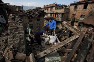 A Nepalese family collects belongings from their home destroyed in Saturday's earthquake, in Bhaktapur on the outskirts of Kathmandu, Nepal, Monday, April 27, 2015. A strong magnitude earthquake shook Nepal�s capital and the densely populated Kathmandu valley on Saturday devastating the region and leaving tens of thousands shell-shocked and sleeping in streets.