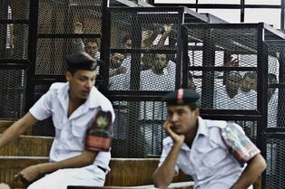 "File - In this file photo taken Thursday, May 15, 2014, Al-Jazeera's Egyptian journalist Abdullah Elshamy, center, appears in a defendants' cage along with several other defendants in a courthouse during a trial on terror charges in Cairo, Egypt. On Wednesday, July 23, an Egyptian judge released his reasoning for harsh sentences issued against three Al-Jazeera journalists, saying they were brought together ""by the devil"" to fake news reports with the aim of destabilizing the country. (AP Photo/Hamada Elrasam, File)"