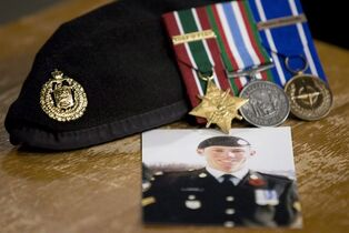 A photo of Cpl. Stuart Langridge is seen along with his beret and medals at a news conference on Parliament Hill in Ottawa, Thursday October 28, 2010. A long-awaited report into whether the military botched its investigation into the suicide of Cpl. Langridge, a troubled young soldier, will be released next week. THE CANADIAN PRESS/Adrian Wyld