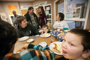 Diana Chartrand (far right) chats with friends while sharing a meal with her partner Bill Trnka (seated, left) and her five children at the West Broadway Community Ministry.
