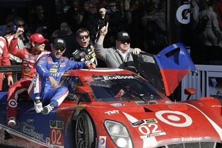 Scott Dixon, of New Zealand, drives the Ford DP to Victory Lane with co-drivers, sitting on the car from left, Kyle Larson, Tony Kanaan, Jamie McMurray and car owner Chip Ganassi after winning the IMSA 24 hour auto race at Daytona International Speedway, Sunday, Jan. 25, 2015, in Daytona Beach, Fla. (AP Photo/John Raoux)