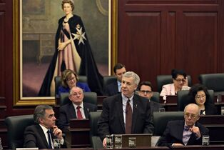 Alberta Premier Jim Prentice, left, and Minister of Health Stephen Mandel, right, watch as Finance Minister Robin Campbell delivers the 2015 budget in Edmonton, Alta., on Thursday, March 26, 2015. THE CANADIAN PRESS/Jason Franson