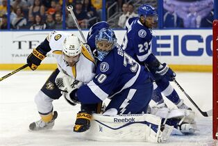 Nashville Predators' Paul Gaustad, left, crashes into Tampa Bay Lightning goalie Ben Bishop after tipping in a puck to score as J.T. Brown (23) looks on during the first period of an NHL hockey game Thursday, March 26, 2015, in Tampa, Fla. (AP Photo/Mike Carlson)