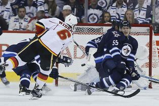 Calgary's Dennis Wideman gets the Flames on the board in the second, blasting a puck past Winnipeg Jets goaltender Ondrej Pavelec as Mark Scheifele (55) tries in vain to block the shot.