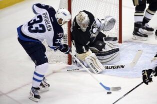 Winnipeg Jets' Dustin Byfuglien (33) can't get a shot off in front of Pittsburgh Penguins goalie Thomas Greiss during the first period in Pittsburgh Tuesday.