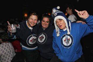 Jets fans Debbie Dutka (from left), Tracy Schaldemose and Heather Foster cheer during a break in play while they watched the game at the Park Theatre in Winnipeg Thursday night.