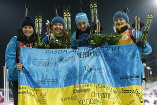 FILE - In this Friday, Feb. 21, 2014, file photo Ukraine's relay team Vita Semerenko, Juliya Dzhyma, Olena Pidhrushna and Valj Semerenko, from left, celebrate with a Ukrainian flag with writings on it after winning the gold during the women's biathlon 4x6k relay, at the 2014 Winter Olympics in Krasnaya Polyana, Russia. With the crisis in Ukraine escalating by the day, the prospect of holding the Winter Olympics in the former Soviet republic seems hard to imagine. Yet, the western Ukrainian city of Lviv hasn't given up on its bid for the 2022 Games. Lviv remains among the five contenders in what is turning into a very unstable race, vying with Almaty, Kazakhstan; Beijing; Krakow, Poland; and Oslo. (AP Photo/Dmitry Lovetsky, File)