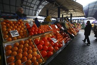 In this Thursday, Dec. 11, 2014 photo a Belarusian man examines imported fruit at the central market Komarovka in Minsk, Belarus. Belarus has profited handsomely on its new role of a key conduit for European food banned by Moscow in retaliation to Western sanctions.(AP Photo/Sergei Grits)