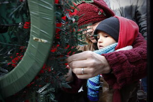 A mother and child place a poppy on a wreath during a Remembrance Day service in Winnipeg, Tuesday, November 11, 2014.