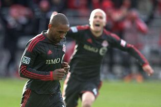 Toronto FC 's Jermain Defoe celebrates after scoring against D.C. United as Michael Bradley (right) runs in during second half MLS action in Toronto on Saturday, March 22, 2014. Defoe has booked his ticket to Toronto. Meanwhile, fellow Toronto FC star Michael Bradley wants fans to help the team in its playoff push by showing the home side some love Sunday when hapless Chivas USA comes to visit. THE CANADIAN PRESS/Chris Young