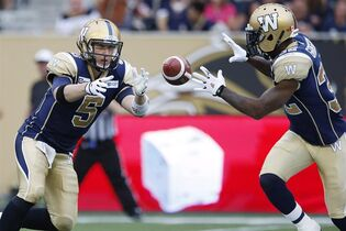 Winnipeg Blue Bombers quarterback Drew Willy (5) tosses the ball to Nic Grigsby (32) during the first half of CFL action in Winnipeg Saturday, September 27, 2014. THE CANADIAN PRESS/John Woods
