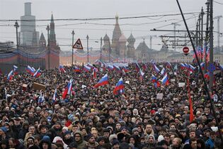 """People carry Russian national flags during a march in memory of opposition leader Boris Nemtsov who was gunned down on Friday, Feb. 27, 2015 near the Kremlin, with The Kremlin Wall and St. Basil Cathedral in the background in Moscow, Russia, Sunday, March 1, 2015. Thousands converged Sunday in central Moscow to mourn veteran liberal politician Boris Nemtsov, whose killing on the streets of the capital has shaken Russia's beleaguered opposition. They carried flowers, portraits and white signs that said """"I am not afraid."""" (AP Photo/Dmitry Lovetsky)"""