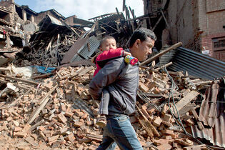 A Nepalese man carries a child as he walks past destroyed buildings that collapsed in Saturday's magnitude-7.8 earthquake, in Bhaktapur, on the outskirts of Kathmandu, Nepal, on Monday.