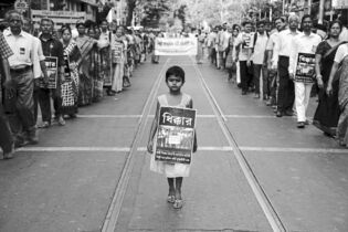A girl walks in protest against the gang rape of a nun in Kolkata, India. The poster reads 'Shame.'