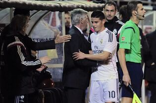 Real Madrid's James Rodriguez, second right, is congratulated by his head coach, Carlo Ancelotti of Italy, after his substitution during their La Liga soccer match against SD Eibar, at Ipurua stadium in Eibar, northern Spain, Saturday Nov. 22, 2014. (AP Photo/Alvaro Barrientos)
