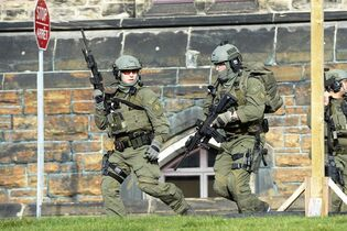 An RCMP intervention team run next to a Parliament building in Ottawa Wednesday Oct.22, 2014. A Canadian soldier standing guard at the National War Memorial in Ottawa has been shot by an unknown gunman and there are reports of gunfire inside the halls of Parliament. THE CANADIAN PRESS/Adrian Wyld