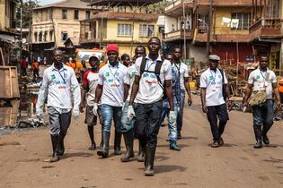 A team of Sierra Leone health workers walk as they look for people suffering from Ebola virus symptoms or people they can educate about the virus as their country enters a three day country wide lockdown on movement of people due to the Ebola virus in the city of Freetown, Sierra Leone, Friday, March. 27, 2015. Sierra Leone's 6 million people were told to stay home for three days, except for religious services, beginning Friday as the West African nation attempted a final push to rid itself of Ebola. (AP Photo/ Michael Duff)