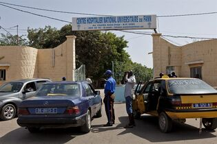 """In this photo taken on Friday, Aug. 29, 2014, a security guard, center left, working at the University Hospital Fann, speaks to people inside a car, as a man is treated for symptoms of the Ebola virus inside the Hospital in Dakar, Senegal. The effort to contain Ebola in Senegal is """"a top priority emergency,"""" the World Health Organization said Sunday, as the government continued tracing everyone who came in contact with a Guinean student who has tested positive for the deadly disease in the capital, Dakar. (AP Photo/Jane Hahn)"""