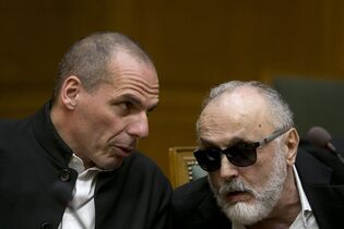 Greek Finance Minister Yanis Varoufakis, left, chats with Health Minister Panagiotis Kouroublis at a Cabinet Meeting in Athens, on Sunday, March 29, 2015. Greece is going through difficult talks with its lenders with its cash reserves nearly depleted. (AP Photo/Petros Giannakouris)
