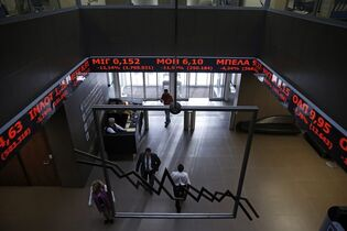 Employees of Athens Stock Exchange walk under screens showing falling stocks in red on Wednesday, Jan. 28, 2015. Greece's radical new government on Wednesday signaled the country would backtrack or scrap a series of budget measures its eurozone creditor nations had demanded in exchange for bailout loans. (AP Photo/Petros Giannakouris)