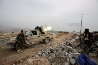 In this Thursday Jan. 29, 2015 photo, a Kurdish peshmerga fighter fires a weapon towards positions of the Islamic State group who are 500 meters or half a mile away, overlooking the strategic town of Sinjar, northern Iraq. Peshmerga fighters representing the lawful authorities of Iraqi Kurdistan fume against what they see as the recklessness of their allies in militias drawn from neighboring Syria and Turkey making progress painful and raising doubts about whether these groups can work together. At stake is ownership of Sinjar, the town that once was home to many of Iraq's Yazidi religious minority. (AP Photo/Bram Janssen)