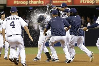 San Diego Padres' Yasmani Grandal, center, is swarmed by teammates after hitting a walk off single to beat the Los Angeles Dodgers in the twelfth inning in a baseball game Friday, Aug. 29, 2014, in San Diego. The Padres won, 3-2. (AP Photo/Gregory Bull)