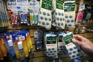In this Jan. 27, 2015 photo, marijuana-themed souvenir socks sold by entrepreneur Ann Jordan are stocked alongside various items by Arnie Slaughter, the owner of the Red Carpet Car Wash and Detailing, in Aurora, Colo. Marijuana is legal in Colorado, but not at its largest airport - and now Denver International Airport wants to keep out weed-themed souvenirs, too. A policy enacted this month bans the sale of souvenirs depicting marijuana leaves or Colorado's ubiquitous