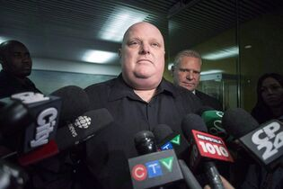 Toronto's outgoing mayor Rob Ford, left, stands next to his brother Doug Ford outside his office as he scrums with the media in Toronto on November 21, 2014. Former Toronto mayor Rob Ford has issued yet another public apology, this time for racial slurs he used during his term as the leader of Canada's largest city. Ford, who is now a city councillor, says he's aware of the