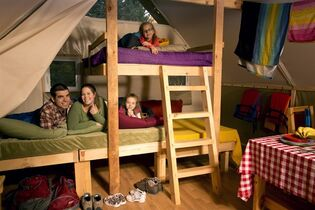 A family poses on bunk beds inside of an oTENTik, a cross between a tent and cabin, at La Mauricie National Park in Quebec in this undated handout photo. THE CANADIAN PRESS/HO - Parks Canada